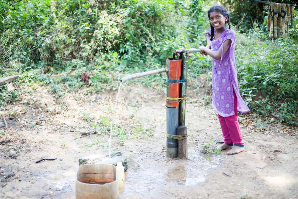 Girl smiling at the camera as she pumps water into a wooden bucket that is on the ground. She is wearing pink pants and a purple dress. There are trees in the background.