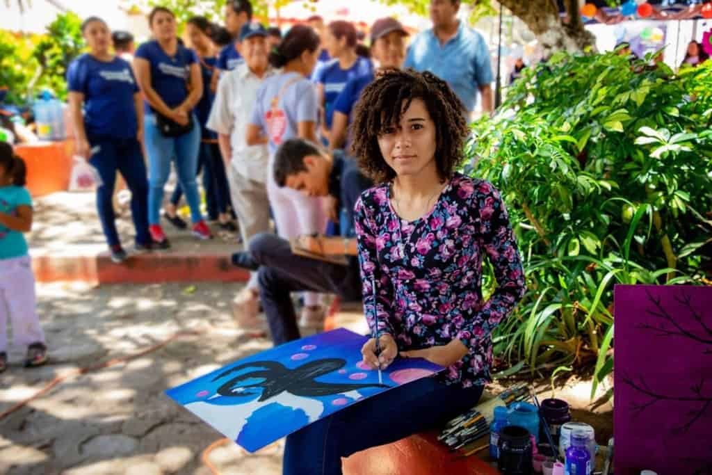 Sandra is wearing a black dress with pink and blue flowers on it. She is painting at the craft fair and she is sitting in front of a tree. There are many other people in the background.