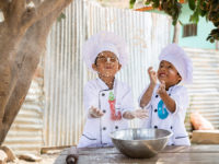 Two twin boys in Bolivia are wearing chef outfits and tossing flour into the air.
