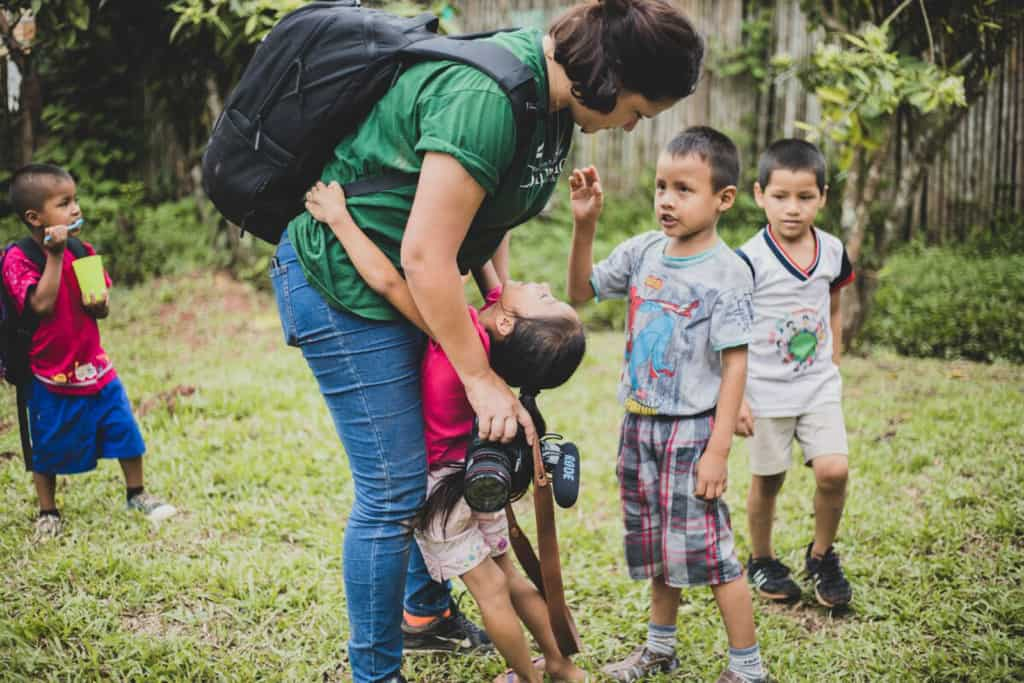 Sara Navarro, Compassion photojournalist leans over to hug a child while holding her camera and wearing a backpack. Other children walk in the grass on the background.
