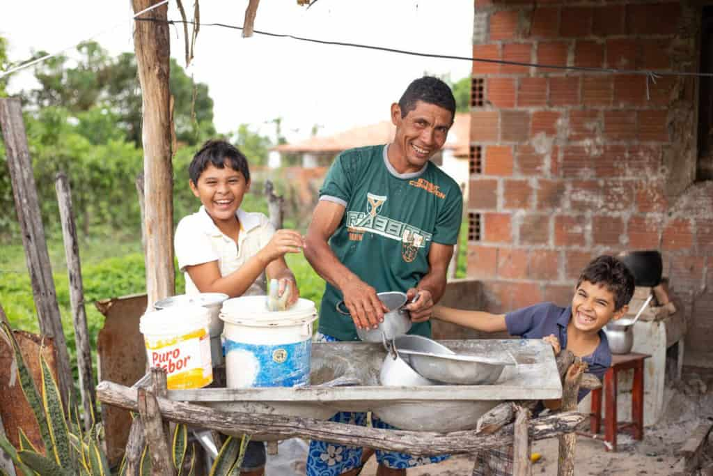 Damião, wearing a green shirt, is with his sons, Davi, wearing a white shirt, and Luan, wearing a blue shirt. They are washing dishes together in their back yard.