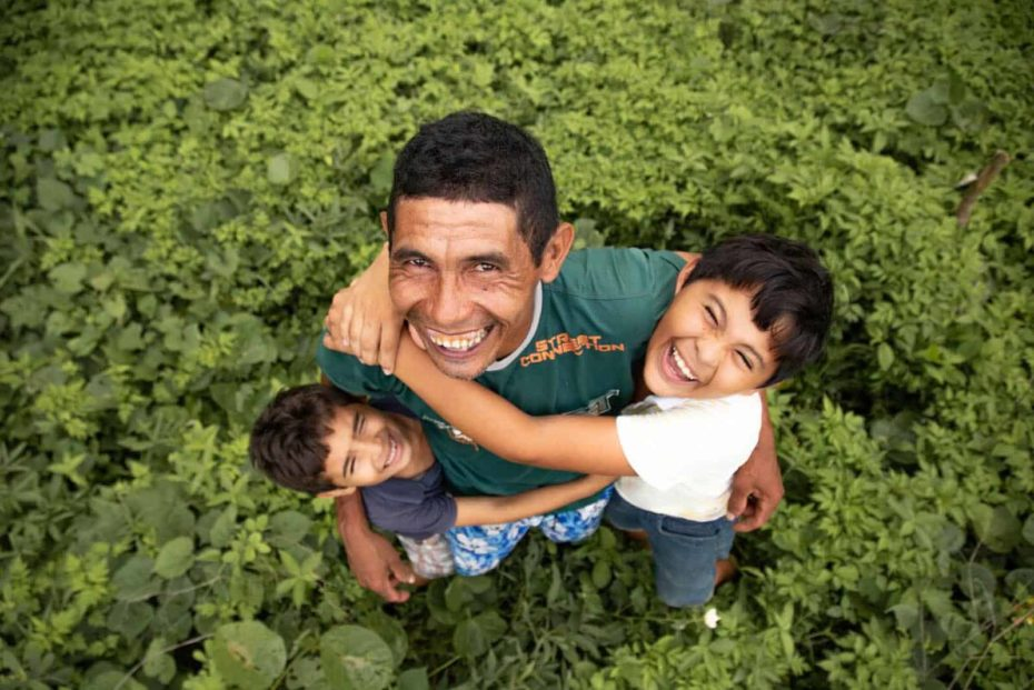 Damião, wearing a green shirt, is with his sons, Davi, wearing a white shirt, and Luan, wearing a blue shirt. They are hugging each other in their back yard. They are standing in the grass.