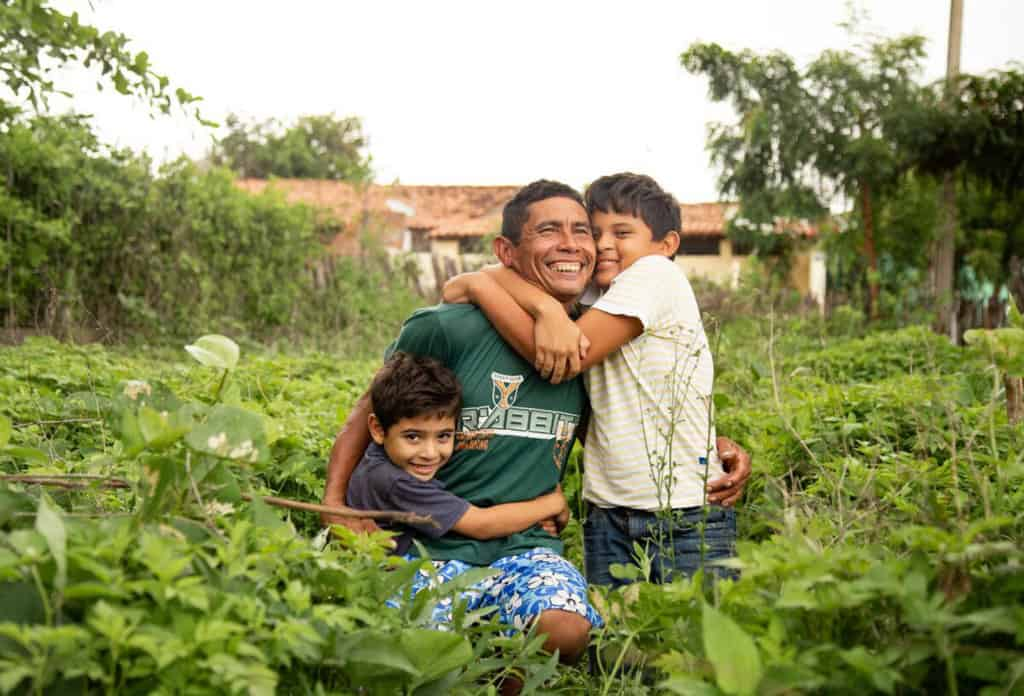 Damião, wearing a green shirt, is with his sons, Davi, wearing a white shirt, and Luan, wearing a blue shirt. They are kneeling down in the grass in their backyard and are hugging each other.