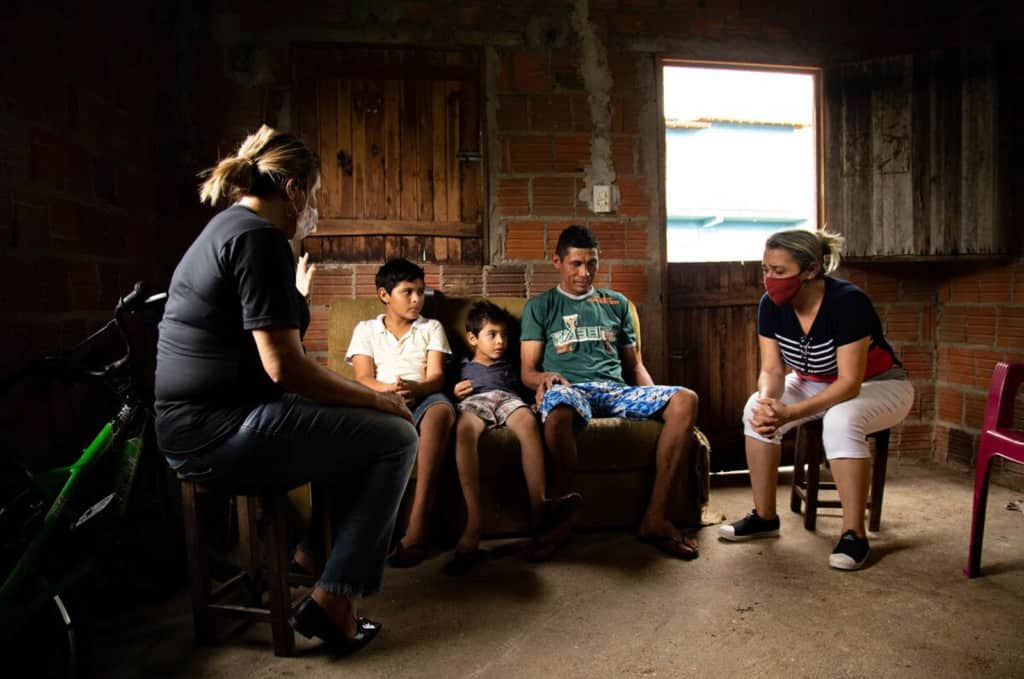 Damião, wearing a green shirt, is with his sons, Davi, wearing a white shirt, and Luan, wearing a blue shirt. They are sitting inside their home with two Compassion volunteers who are praying for them. The volunteers are wearing face masks.