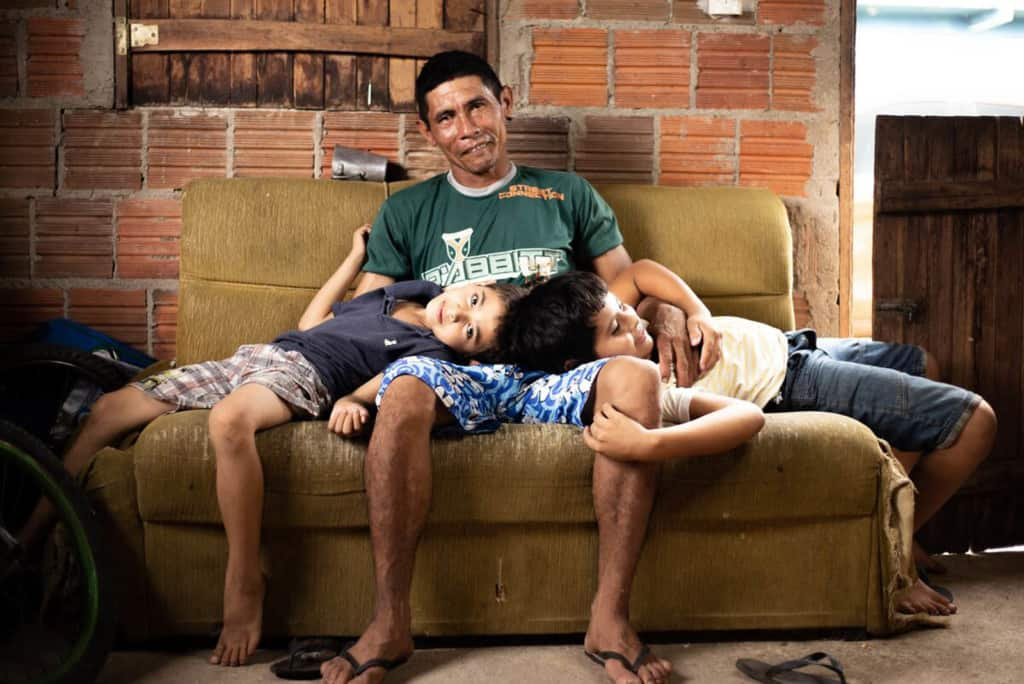 Damião, wearing a green shirt, is with his sons, Davi, wearing a white shirt, and Luan, wearing a blue shirt. They are sitting together on a couch in their home and Davi and Luan are resting their heads in their dad's lap.