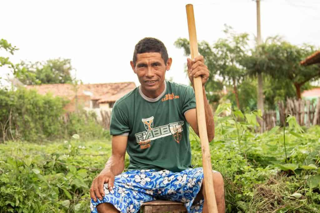 Damião, wearing a green shirt and blue patterned shorts, is sitting on a stool outside in his back yard. He is holding a large stick