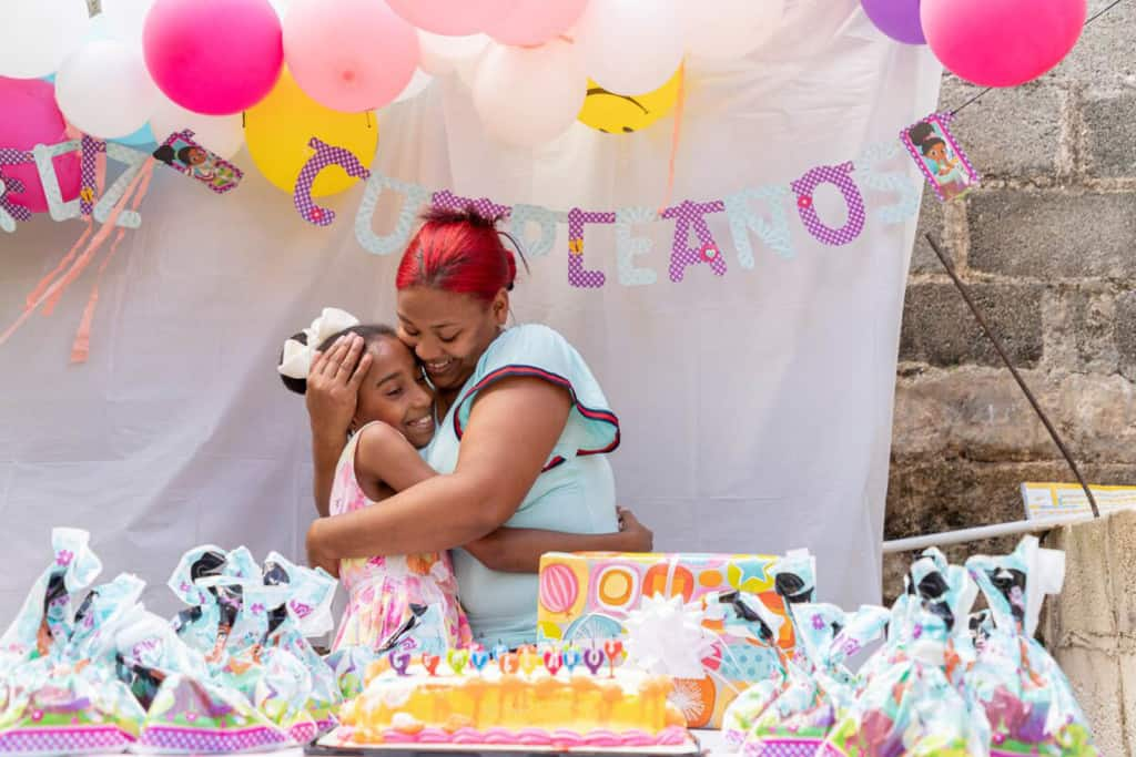 """Lorielky is wearig a white dress with pink and orange flowers. She is standing behind a table with a birthday cake and gifts on it. Abover her are colorful balloons and behind her is a sign that says, """"Cumpleanos."""" She is hugging her mother, Delmi."""