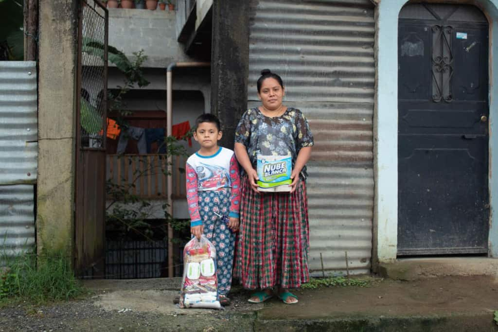 Elfego and his mother Amelia stands outside the room they are renting while they wait for the water level to lower at their house.