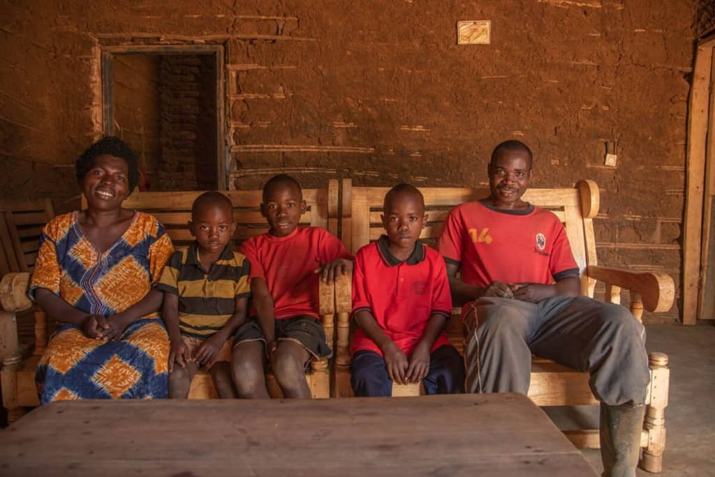 Frank is wearing a red shirt and dark shorts. He is sitting on a bench with his family in front of their home, which has been renovated using money from a gift from Frank's sponsor.