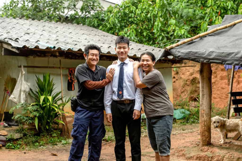 A family portrait of Surayut wearing his school uniform with his parent with smile, standing in front of his house.