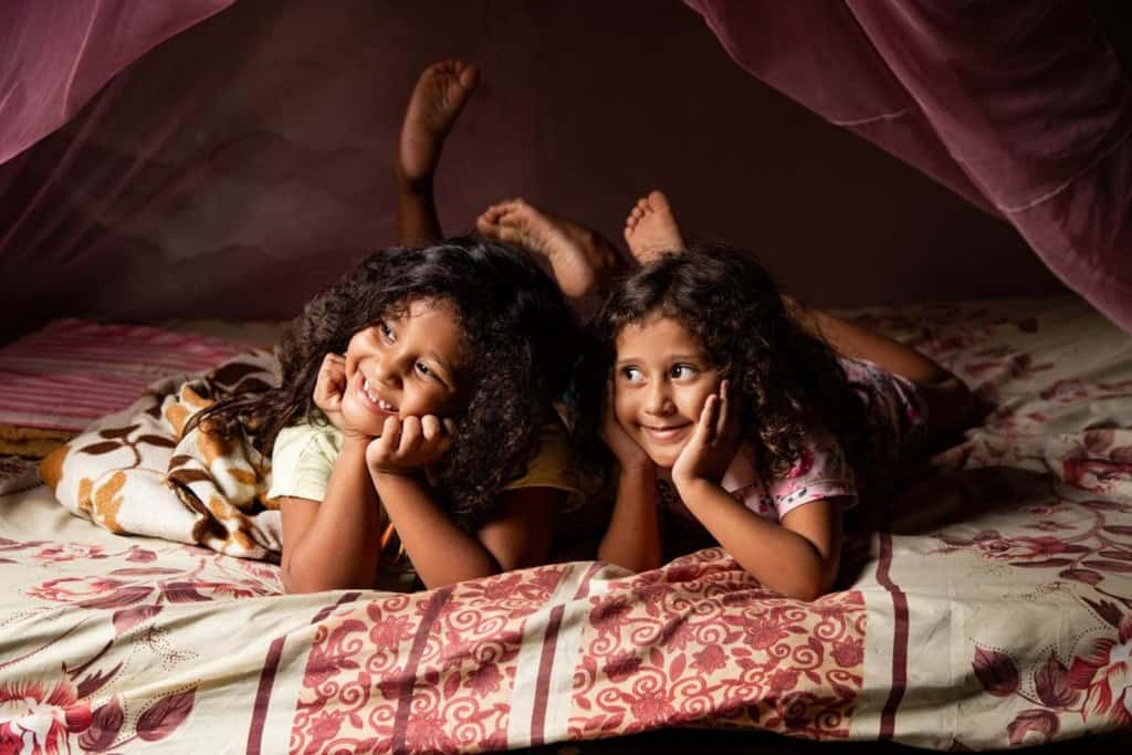Sophia is wearing a cream colored shirt and shorts. She is laying on her bed and there is a pink mosquito net above her. Next to her is her sister, Daphyne. Both of them are resting their hands on their chins.