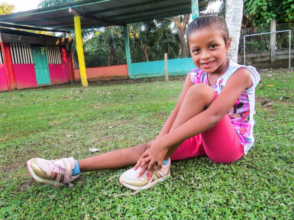 Iris is wearing a brightly colored shirt and pink shorts. She is sitting in the yard of the Compassion center and is showing off her new shoes.