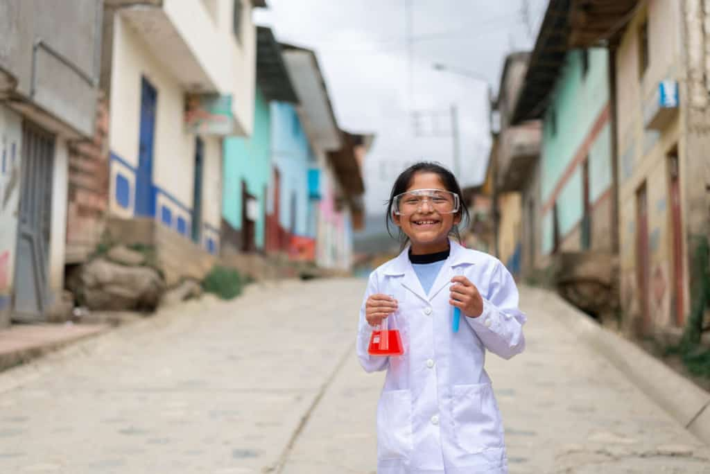 Girl wearing white scientist costume and holding test tubes in the streets of Huarichaca.
