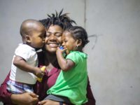 A Haitian woman smiles and holds her twin toddlers