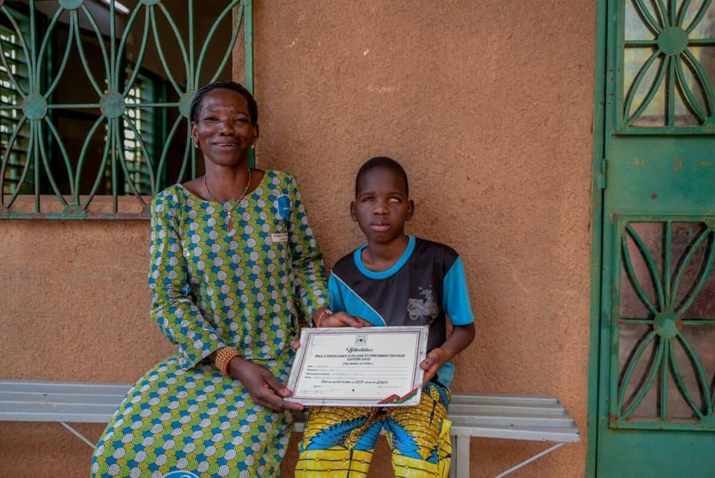 A strong mother wearing a green, blue and white dress smiles proudly as she and her son hold up a certificate of recognition of academic excellence from Burkina Faso's president.