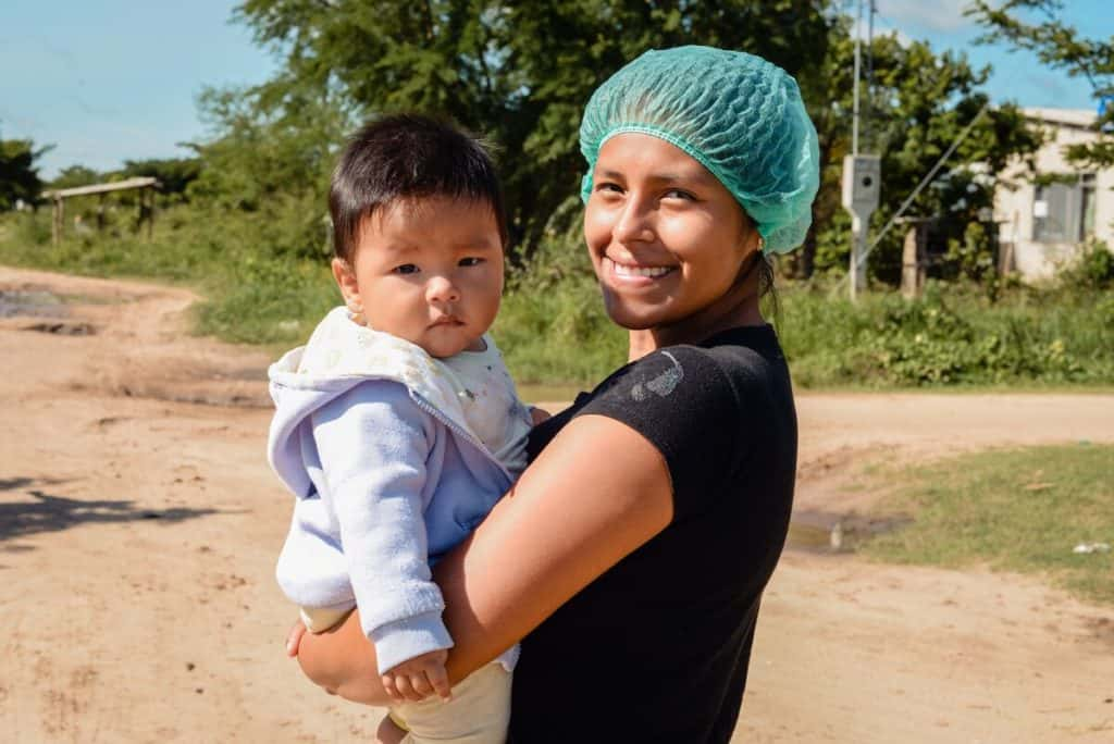 A teen mom in Bolivia wearing a green hair net and black shirt holds her young child.