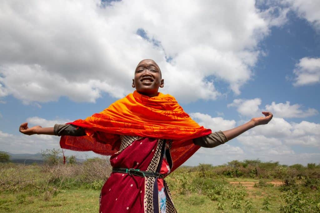 A Kenyan boy in orange and red clothing holds his hands out and smiles. His eyes are closed and he is gazing upward