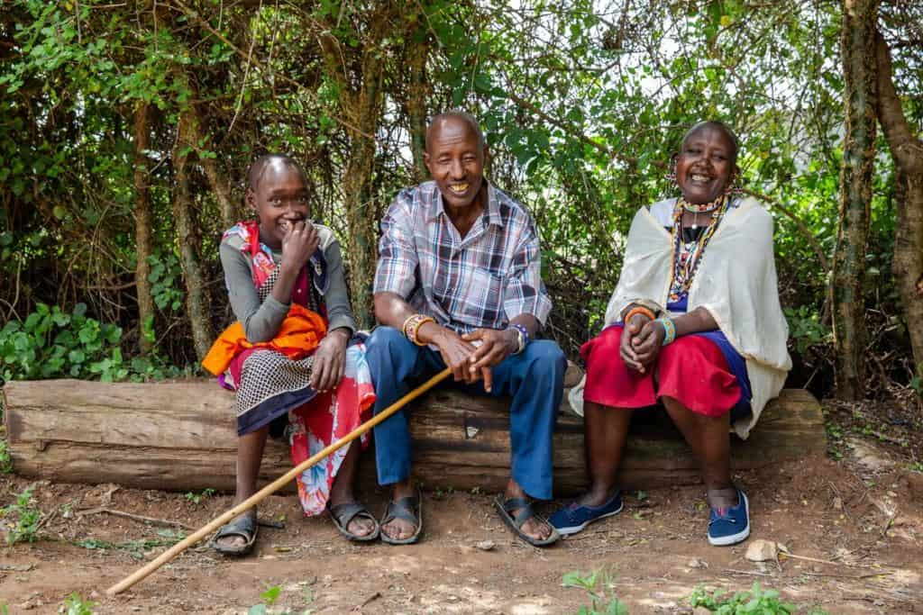 A teenage boy and his two parents sit on a log outside. They are all smiling.