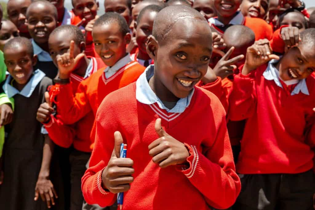 A Kenyan teenager gives two thumbs up. A group of children stands smiling behind him. They are wearing red sweaters over white collared shirts.