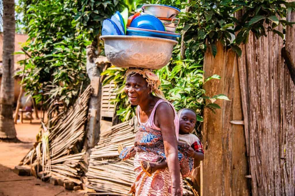 A woman walks with a toddler strapped to her back in a colorful cloth. She is balancing a large pan stacked high with dishes on her head.