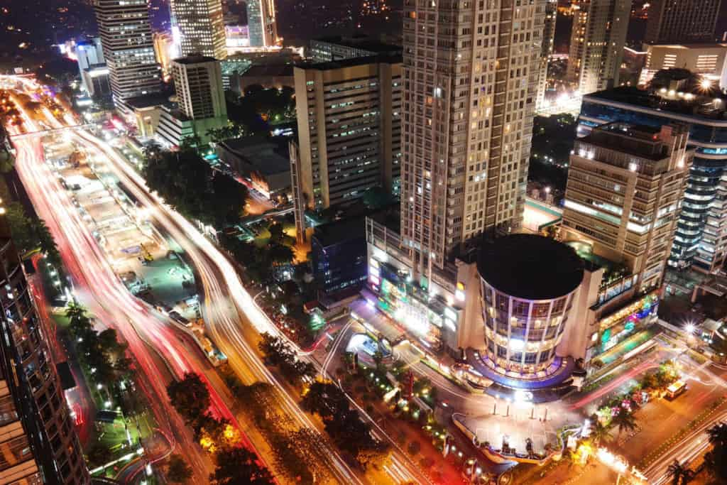 Nighttime in Jakarta. The buildings are lit up and the streets have streaks of lights from vehicles.