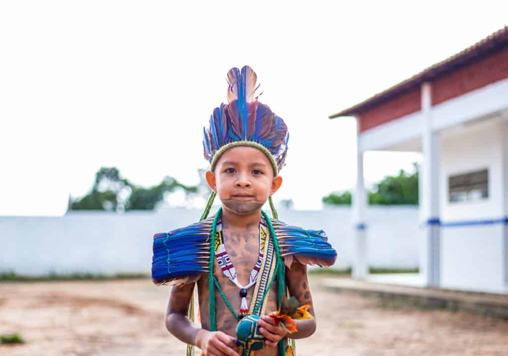 Kaio is standing outside the Compassion center and is wearing a traditional Guajajara costume. He is also holding a rattle. His face and body are painted with designs.