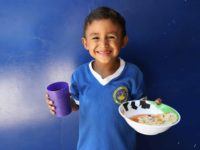 Boy wearing a blue shirt with white collar and the background is a blue wall of the kitchen's front.