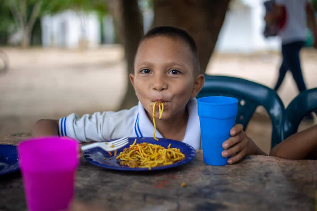 Marcos, wearing a white shirt, is eating spaghetti. He is sitting at a table and is holding a blue cup.