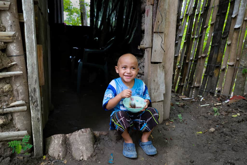 Axel is wearing a light blue and white soccer jersey and black shorts. He is sitting in his house's doorway eating red beans with sour cream, which is one of his favorite foods. There is a fence beside the home.
