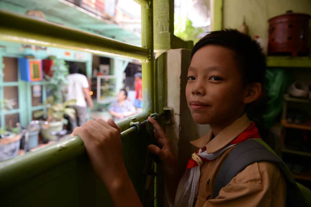 Boy in Jakarta smiles at the camera while wearing a tan shirt and backpack.