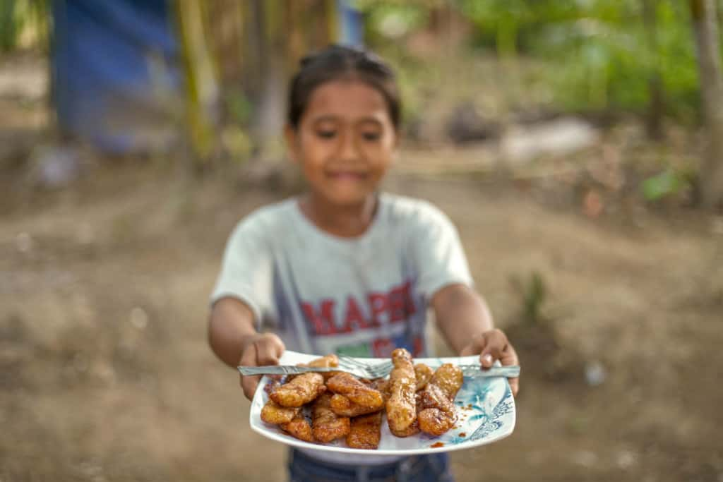 """Angel, in a gray shirt holds and looks at a white and blue plate of """"buchi-buchi"""" in front of her. There is a fork on the plate."""