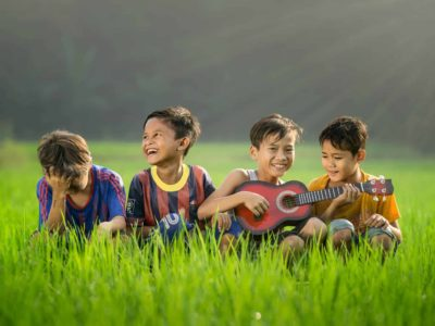 Four boys sitting in a green field. One is playing a small stringed instrument while the others smile and laugh.