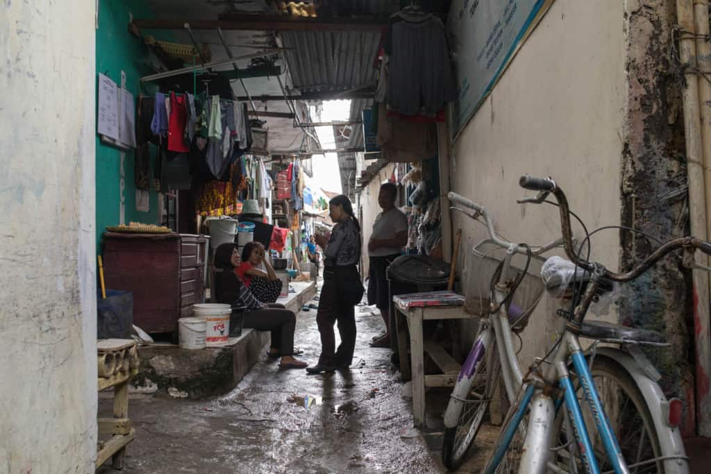 Two bicycles are leaning against a building in a narrow alley in Pulomas, East Jakarta. Four people are in the alley, talking.