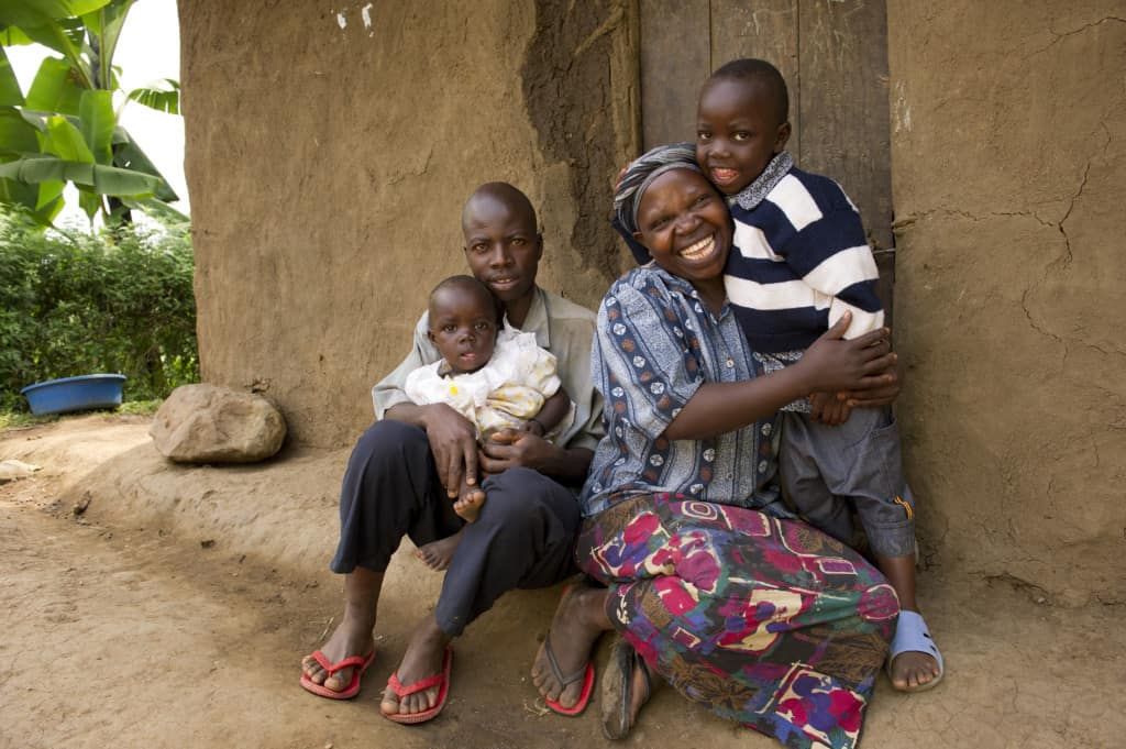 Hadija and her husband sit with their young son and daughter outside their mud home in Uganda