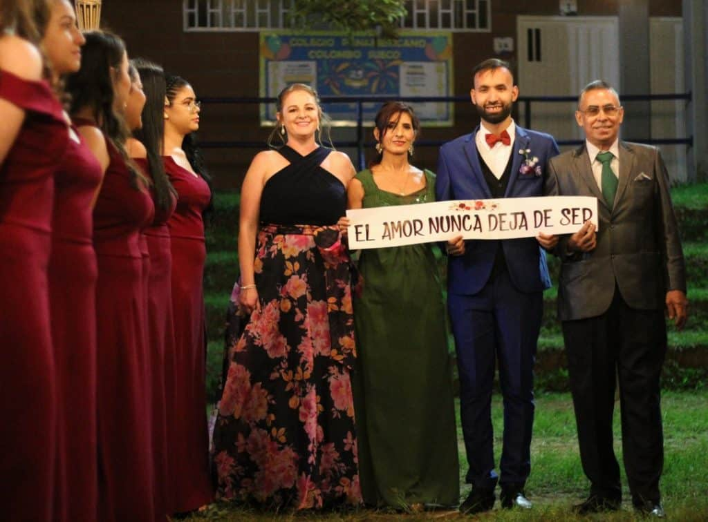 """Two men and two women stands next to each other outdoors at a wedding in Colombia. They are holding a sign that says """"El amor nunca deja de ser,"""" which translates to """"Love never ceases to be"""" in English. There are bridesmaids wearing red dresses lined up near them."""