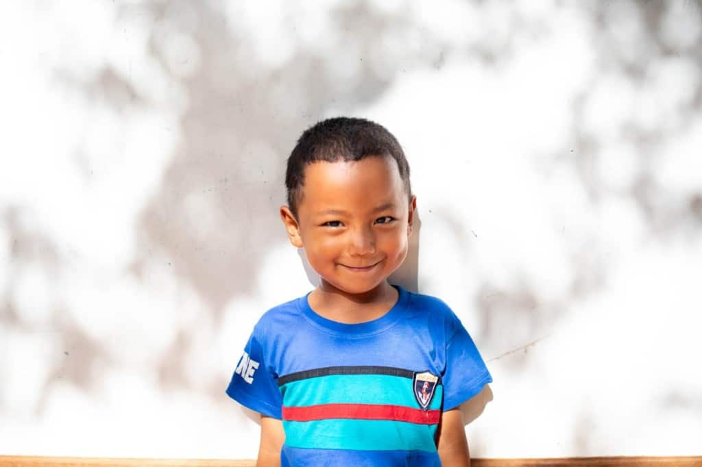 Weeview is wearing a blue shirt with black, green, and red stripes. He is standing in front of a white wall.