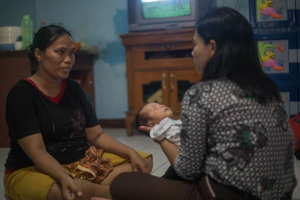 Woman in a black shirt, is sitting at home on the floor with a project staff member who is conducting a home visit after the flood had receded. The staff member is holding baby Gabrian, who is sleeping.