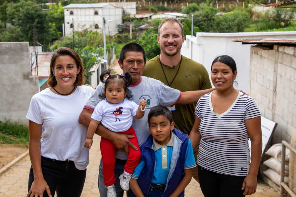 Nate (in khaki green) and Lexi (in white) are standing on a set of steps posing for a photo with a family. The family consists of a dad, mom and two children, a baby girl in red and white, and a boy in blue. There are white buildings on either side of them.