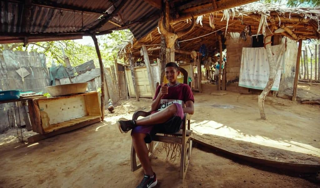 A youth, boy, sits in a wooden chair giving a thumbs up. The floor beneath him is sand, and you can see the thatch roof of the home where he lives in Colombia.