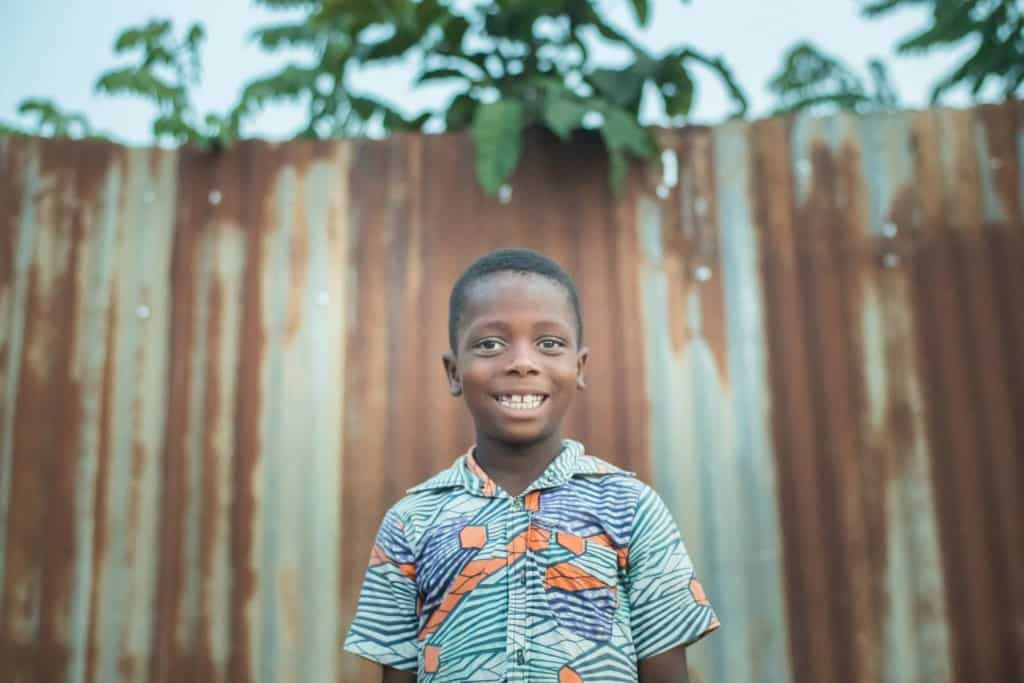 Boy wearing a blue and orange pattern shirt smiles standing outside with a metal rusted fence in the background.
