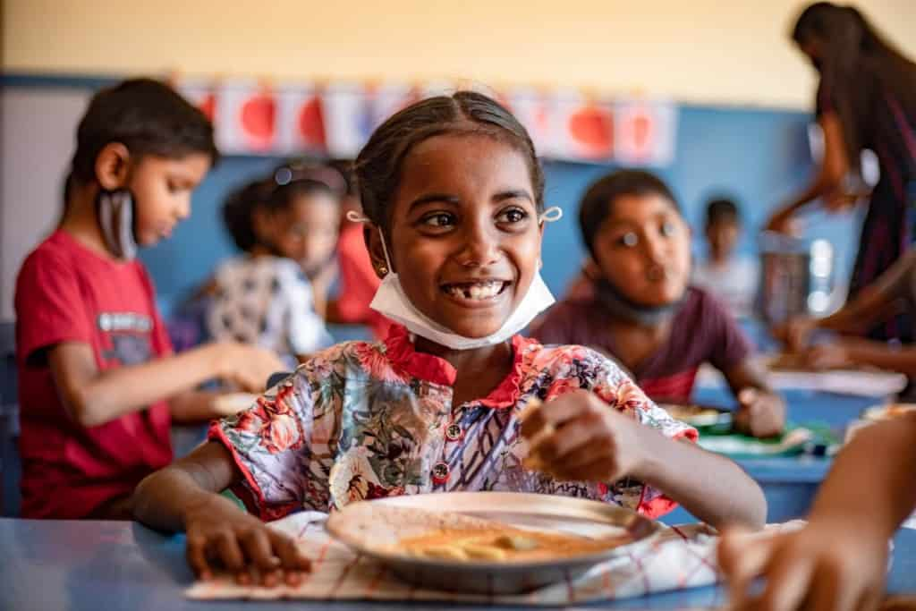 Theresa is wearing a colorfully patterned dress. She is sitting down at a table with a plate of food in front of her. The meal for the day included dosai, lentils curry and coconut chutney, most of the children's favorite dish.