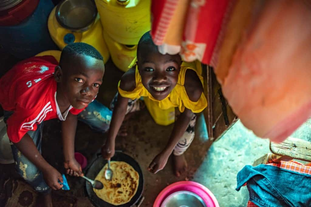 Leach and Moses are seen here helping to make Chapati, one of their favorite foods. They are looking up at the camera and smiling.