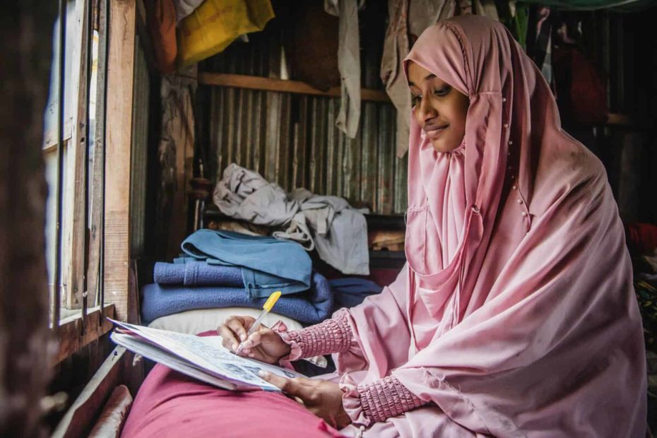 Woman wearing a pink dress and head covering. She is sitting in front of a window in her home and is writing a letter to her sponsor.