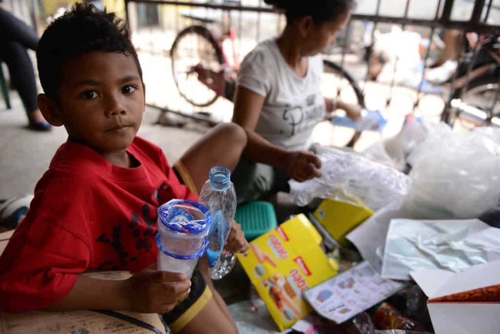 7-year-old boy in Jakarta holds empty plastic cups and a plastic bottle and makes eye contact. An adult female behind him sorts recyclables.
