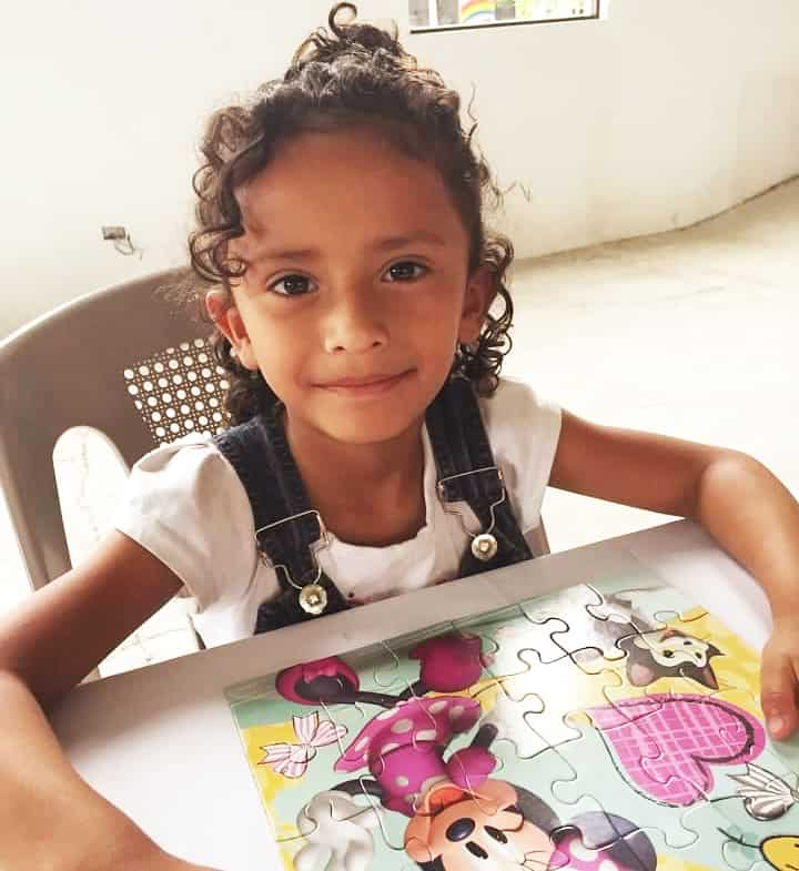 Genesis, a young girl with curly hair, sits by a completed Minnie Mouse puzzle.