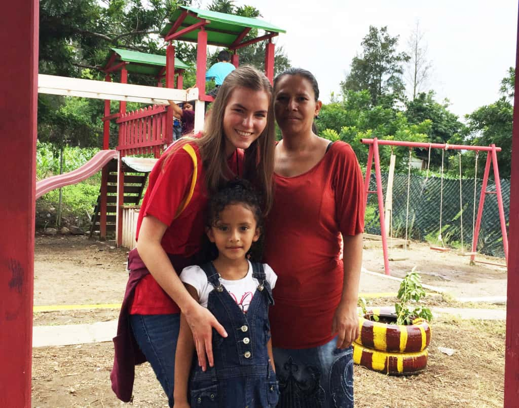 Two women, Hayli and Imelda, stand with a young girl, Genesis. There is a swing set in the background. The women are wearing red shirts, and the girl is wearing overalls.