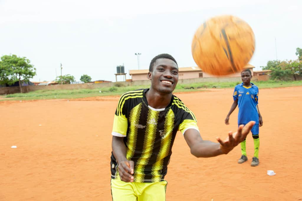 An action shot of a twenty-one-year-old adult male wearing a black and yellow soccer uniform, jersey, juggling, throwing a soccer ball in the air. He is standing on a dirt soccer field.