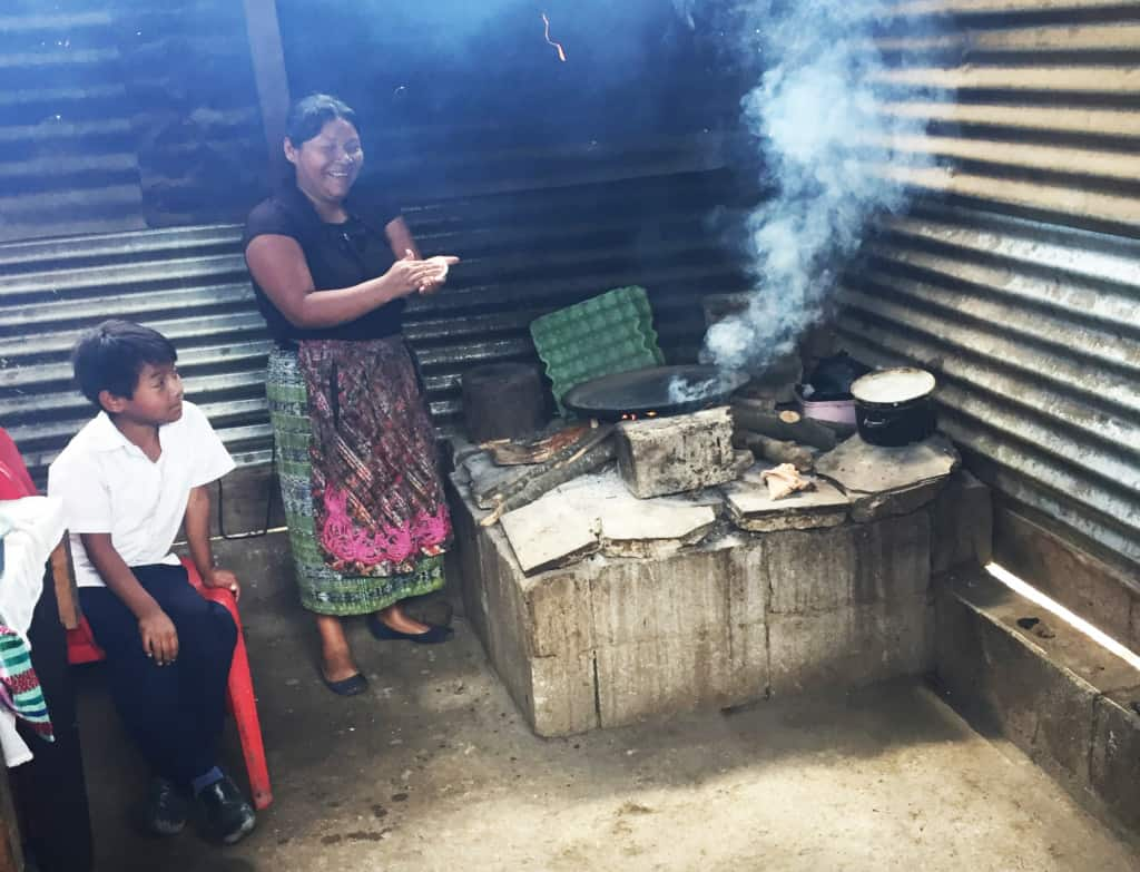 A mother wearing a black shirt and long skirt cooks in a Guatemalan kitchen.