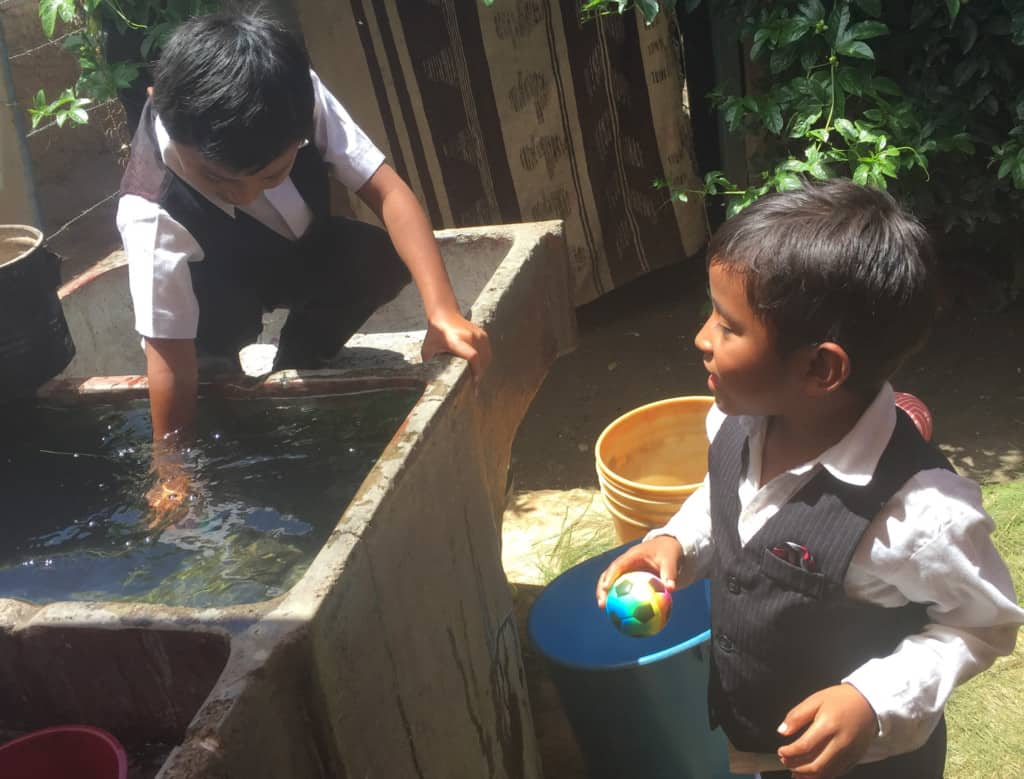Two young boys are wearing vests and white collared shirts. One is holding a toy soccer ball. One is putting his hand into an outdoor sink of water.