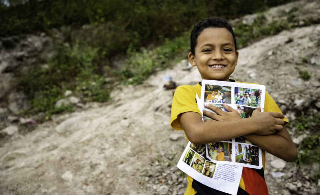 Jairo is wearing a yellow shirt and jeans. He is standing outside his home and is holding his sponsor letters close to his chest.